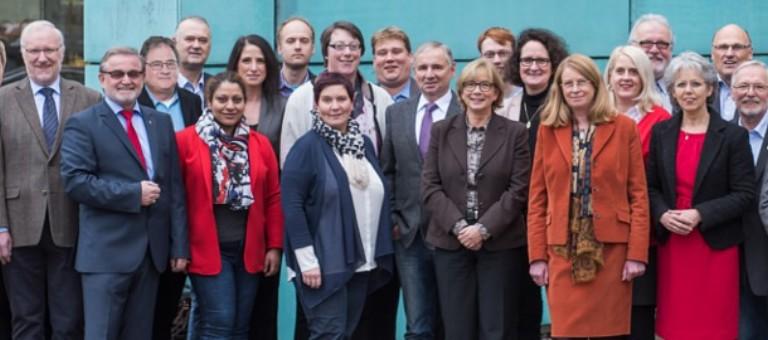 """Man sieht eine Gruppe von lächelnden, jungen Menschen vor einem Tagungszentrum. Man sieht hinten rechts eine Flagge auf der """"Jusos Bezirk Hannover"""" steht."""